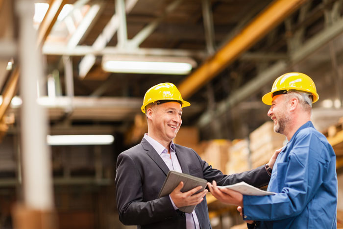 Smiling warehouse manager talking to worker