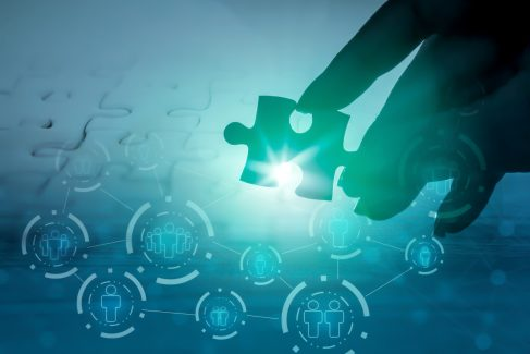 hand holding jigsaw piece with background of teamwork people connection