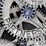 Macro photo of tooth wheel mechanism with Partnership letters imprinted on metal surface