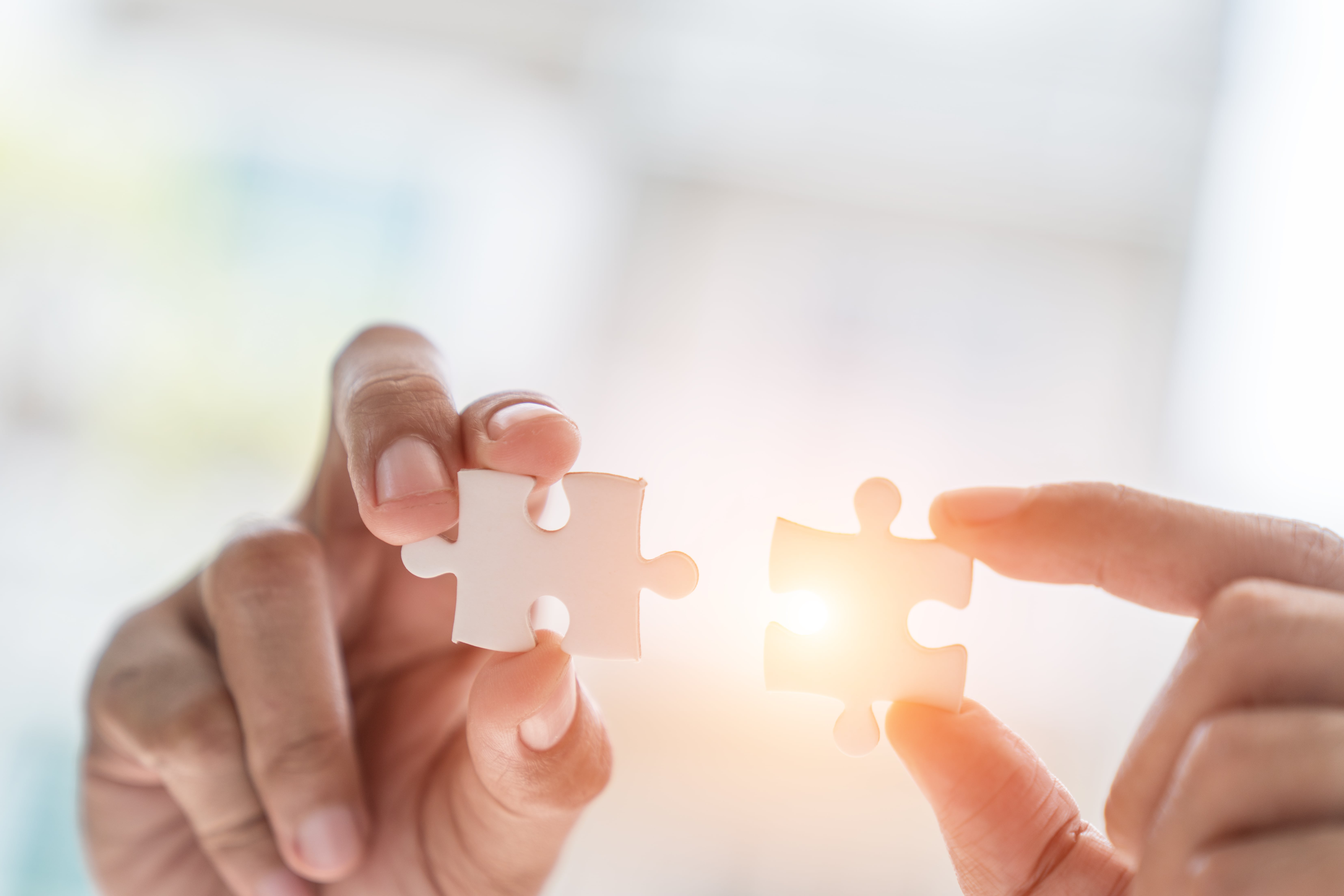 Business solutions, success and strategy concept. Businessman hand connecting jigsaw puzzle.