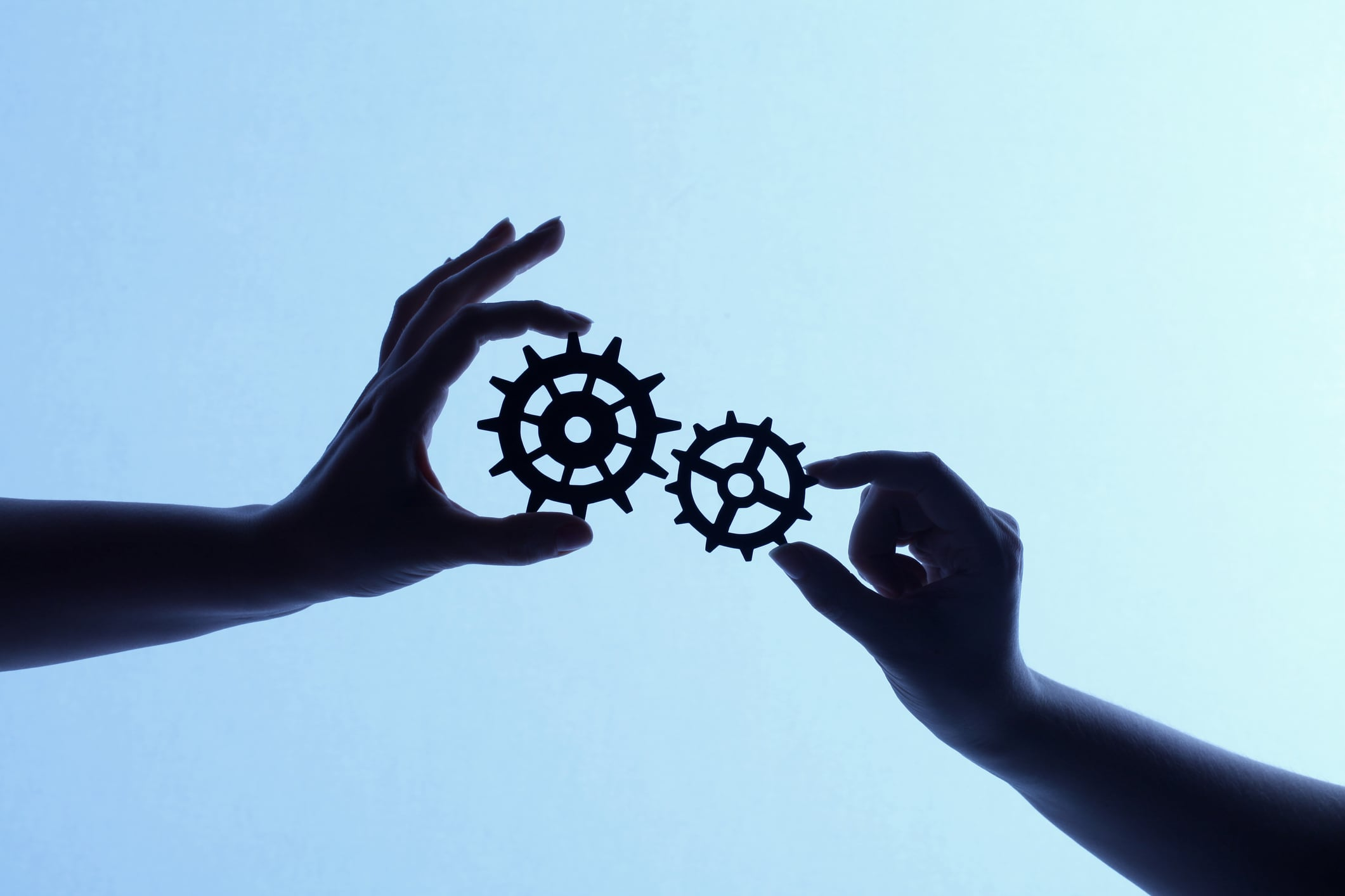 Image showing two backlit shilouetted hands holding mechanical style cogs and gears of various sizes on a blue gradient background. Each gear wheel fits together into the larger system creating the idea of teamwork and cooperation. http://i119.photobucket.com/albums/o144/mattjea/Gears.jpg