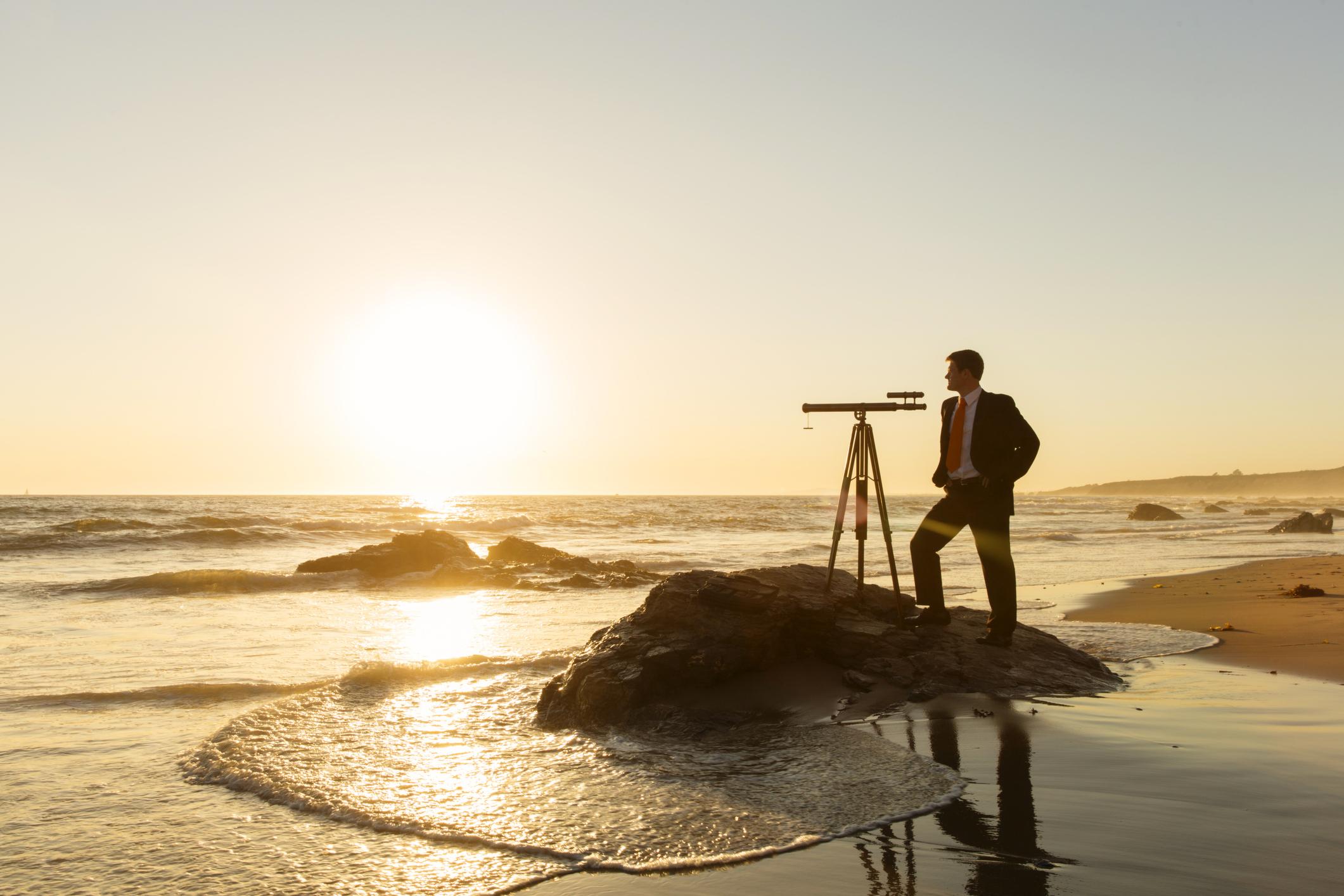 Businessman with Telescope on California Beach
