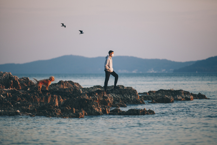 A boy with a protective medical mask, he enjoys sunset with his dog on a rocky shore.