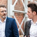 Two businessmen walking and talking at an old brick building